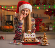 Happy teenage girl in santa hat with christmas cookie house Royalty Free Stock Photography