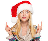 Happy teenage girl in santa hat pointing on copy space Royalty Free Stock Images