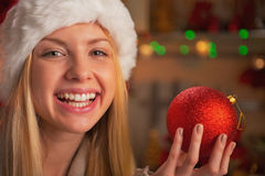 Happy teenage girl in santa hat showing christmas ba Stock Image