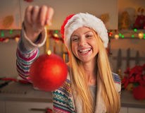 Happy teenage girl in santa hat showing christmas ball Royalty Free Stock Photos