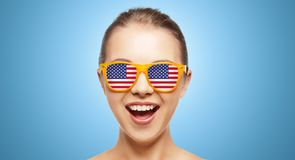Happy teenage girl in shades with american flag. People, patriotism, national pride and independence day concept - happy teenage girl in shades with american stock photography