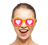 Happy teenage girl in shades with hearts. Love, happiness and people concept - portrait of happy teenage girl in shades with hearts Stock Photography