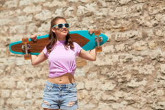 Happy teenage girl in shades with longboard. Lifestyle, longboarding, summer and people concept - smiling young woman or teenage girl in sunglasses with Royalty Free Stock Photos