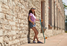 Happy teenage girl in shades with longboard. Lifestyle, summer and people concept - smiling young woman or teenage girl in sunglasses with longboard on city Stock Photo