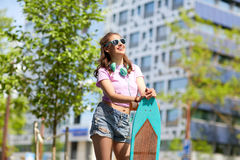 Happy teenage girl in shades with longboard. Lifestyle, summer and people concept - smiling young woman or teenage girl in sunglasses with longboard on city Stock Image