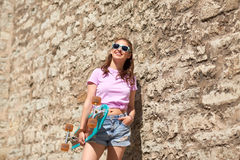Happy teenage girl in shades with longboard. Lifestyle, summer and people concept - smiling young woman or teenage girl in sunglasses with longboard over stone Royalty Free Stock Photography