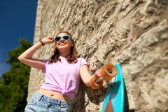 Happy teenage girl in shades with longboard. Lifestyle, summer and people concept - smiling young woman or teenage girl in sunglasses with longboard over stone Stock Photography