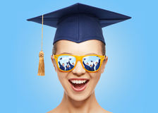 Happy teenage girl in shades and mortarboard hat. Graduation, education, school and people concept - happy screaming teenage girl in shades and mortarboard or Royalty Free Stock Photography