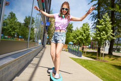 Happy teenage girl in shades riding on longboard. Lifestyle, longboarding and people concept - smiling young woman or teenage girl in sunglasses riding on Stock Images