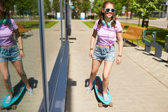 Happy teenage girl in shades riding on longboard. Lifestyle, longboarding and people concept - smiling young woman or teenage girl in sunglasses riding on Royalty Free Stock Photo