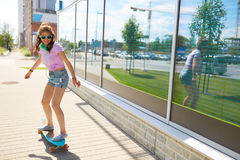 Happy teenage girl in shades riding on longboard. Lifestyle, longboarding and people concept - smiling young woman or teenage girl in sunglasses riding on Royalty Free Stock Photos