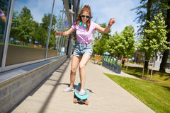 Happy teenage girl in shades riding on longboard. Lifestyle, longboarding and people concept - smiling young woman or teenage girl in sunglasses riding on Royalty Free Stock Photography