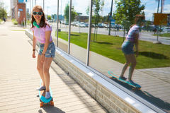 Happy teenage girl in shades riding on longboard. Lifestyle, longboarding and people concept - smiling young woman or teenage girl in sunglasses riding on Stock Photography