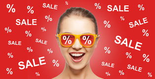 Happy teenage girl in shades with sale signs Stock Images