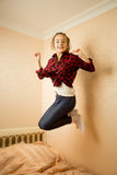 Happy teenage girl in shirt jumping on bed Stock Image