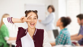 Happy teenage girl showing peace sign at school Royalty Free Stock Photography