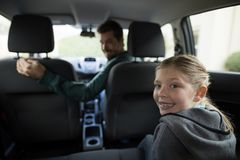 Teenage girl sitting in the back seat while woman driving a car Royalty Free Stock Photo