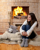 Happy teenage girl sitting fireside Stock Photo
