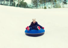Happy teenage girl sliding down on snow tube Stock Images
