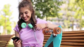 Happy teenage girl with smartphone and longboard stock video footage