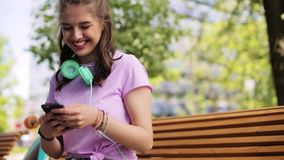 Happy teenage girl with smartphone and longboard stock footage