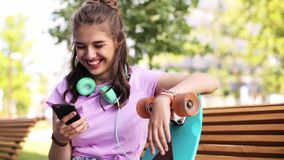 Happy teenage girl with smartphone and longboard. Lifestyle, leisure and people concept - smiling young woman or teenage girl with smartphone, headphones and stock video