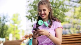 Happy teenage girl with smartphone and longboard. Lifestyle, leisure and people concept - smiling young woman or teenage girl with smartphone, headphones and stock footage