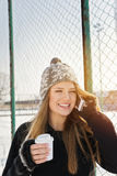 Happy teenage girl speaking on the phone. Cute young Caucasian teenage girl speaking on the phone laughing holding a takeaway coffee cup smiling. Outdoors winter Stock Photo