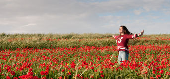 Happy Teenage Girl standing  in a red field of poppy flowers Stock Photos