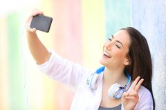 Happy teenage girl taking selfies in a colorful street stock photography