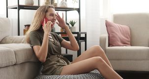 Happy teenage girl talking on mobile phone. Teenage girl laughing while talking on mobile phone at home stock footage