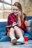 Happy teenage girl talking on smartphone and making notes stock image
