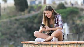 Happy teenage girl texting on phone in a town stock video footage