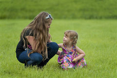 Happy teenage girl and a toddler in the grass stock photo
