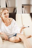 Happy teenage girl with TV remote Stock Photos