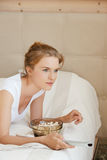 Happy teenage girl with TV remote and popcorn Stock Photo