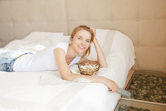 Happy teenage girl with TV remote and popcorn Royalty Free Stock Photos