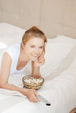 Happy teenage girl with TV remote and popcorn Stock Photography