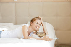 Happy teenage girl with TV remote and popcorn Royalty Free Stock Photo