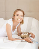 Happy teenage girl with TV remote and popcorn Stock Image