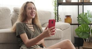 Teenage girl video chatting using mobile phone. Happy teenage girl video chatting using mobile phone at home stock footage