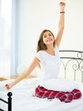 Happy teenage girl waking up and smiling indoors Stock Images