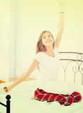 Happy teenage girl waking up and smiling indoors Royalty Free Stock Photography