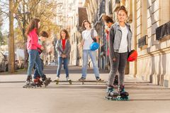 Happy teenage girl in roller skates with friends Royalty Free Stock Image