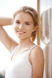 Happy teenage girl at the window Stock Images