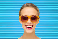 Happy teenage girl or woman face in shades. People, summer accessory and eyewear concept - portrait of happy teenage girl or young woman in shades over blue Royalty Free Stock Photo
