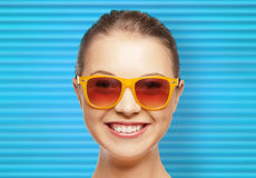 Happy teenage girl or woman face in shades. People, summer accessory and eyewear concept - portrait of happy teenage girl or young woman in shades over blue Royalty Free Stock Images