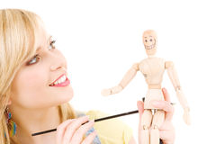 Happy teenage girl with wooden model dummy. Over white Royalty Free Stock Images