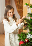 Happy teenage girl in woolen sweater decorating Christmas tree a Stock Image