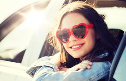 Happy teenage girl or young woman in car. Summer holidays, valentines day, travel, road trip and people concept - happy teenage girl or young woman heart shaped stock images